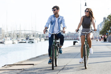 Fototapeta Happy young couple cycling in the city. obraz