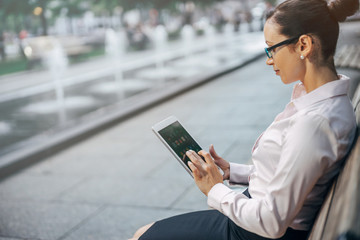 Woman searching information at internet via tablet pc outdoor, Business woman working on a new project and using modern tablet outdoor, blurred background, shallow DOF