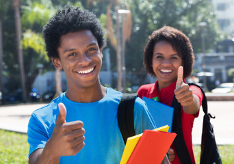 Two happy african american students on campus showing thumbs