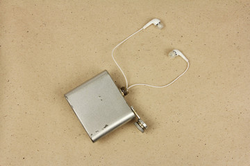 old flask of alcohol with headphones, the idea of addiction