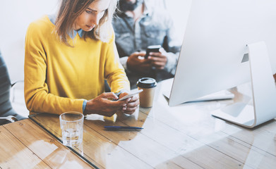 Coworking process in modern office.Woman looking to her mobile phone and sitting at a wooden table.Man typing on his smartphone.Horizontal photo,blurred background.