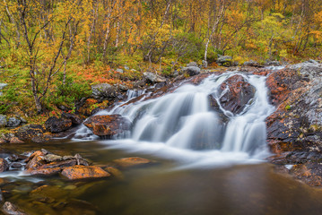 Small waterfall in autumnal landscape