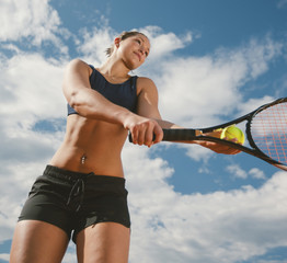 Low angle view of woman playing tennis against sky