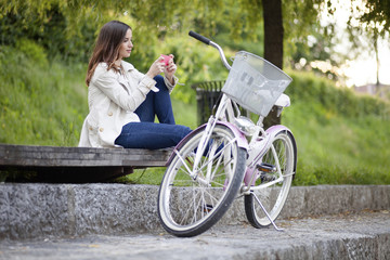 Woman using mobile phone while sitting on plank by bicycle