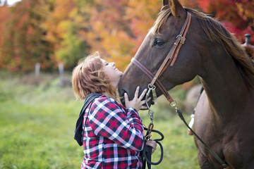 Beautiful and natural adult woman outdoors with horse