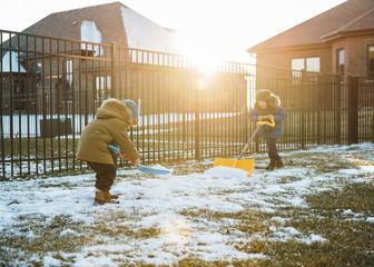 Boys in warm clothing shoveling snow at backyard