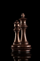Powerful figures / Chess game concept of black wooden king and queen, the most powerful figures standing together against dark background.