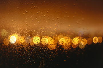 Orange Bokeh on a dark background with drops on glass