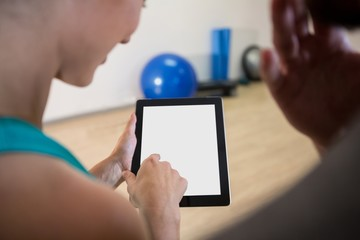 Woman showing digital tablet to fitness trainer
