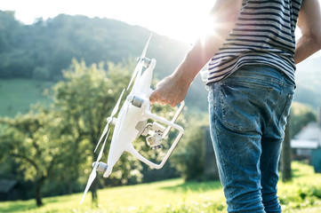 Unrecognizable young man holding drone. Sunny green nature.