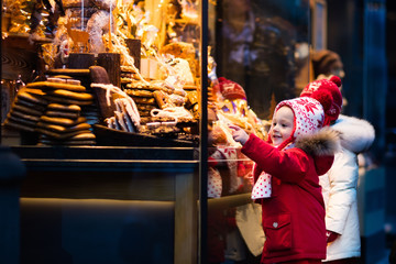 Kids looking at candy and pastry on Christmas market