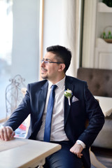 Handsome groom in suit in the hall. Male portrait in the room. Beautiful model boy in colorful wedding clothes. Man is posing. Handsome guy indoors