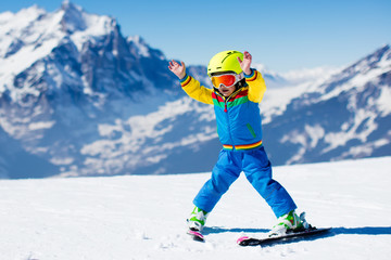 Little child skiing in the mountains Wall mural