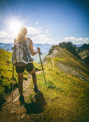 Strong female hiker with backpack pauses on path