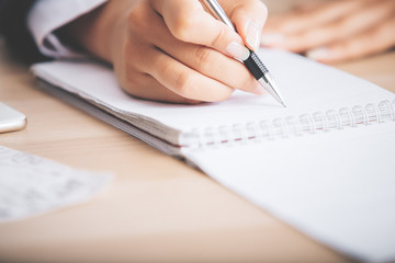 Woman's hand writing in notepad