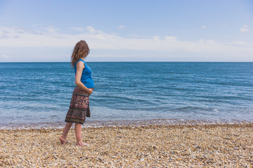 Pregnant woman walking on the beach
