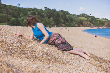 Young woman lying on dune