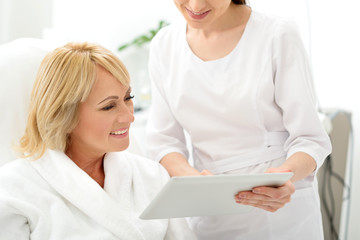 Skillful cosmetician consulting mature lady