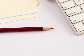 Pencil with keyboard and file folder against white background