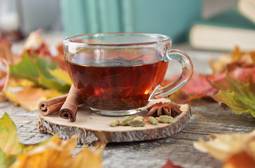 tea cup and autumn leaves on a wooden background