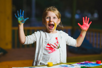 Child having fun painting with finger paint