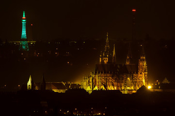 Petrin Lookout Tower  in Saint Patrick Day green color with Prague castle and cathedral at night