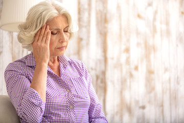 Frustrated old lady has pain in head