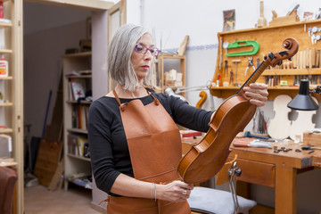 portrait of female mature violin maker while testing the violins