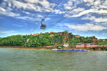 Beautiful HDR image of Fortress Ehrenbreitstein on the mountain in Koblenz over the Rhine river with cable cars moving through mountains. Wall mural