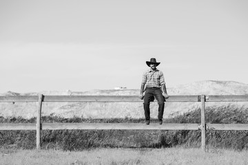 cowboy sitting on a fence