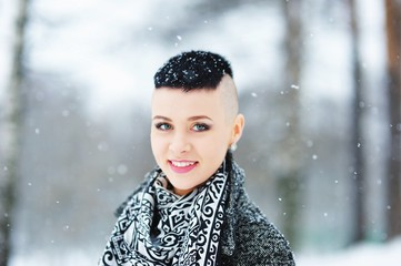 Portrait of a beautiful, cute smiling girl with snowflakes on her hair in the Park against the backdrop of falling snow, close-up.