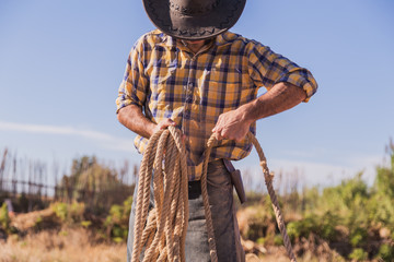 cowboy picking up a rope in the field