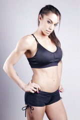 Athletic brunette woman standing, preparing to fight, looking down, over a grey background.