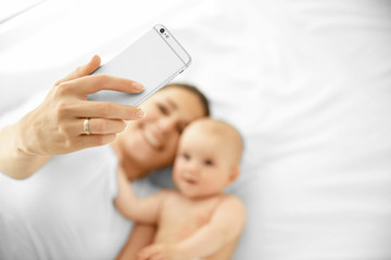 Mother and baby taking selfie on bed