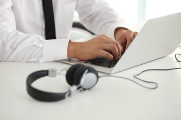 Male hands typing on laptop at office