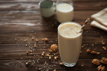 Delicious milkshake with nuts on wooden background