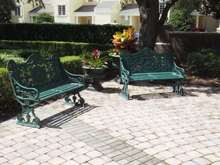 two iron park benches by a patio