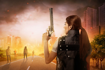 Creepy zombie looking at asian woman holding gun