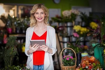 Happy female florist holding digital tablet in flower shop