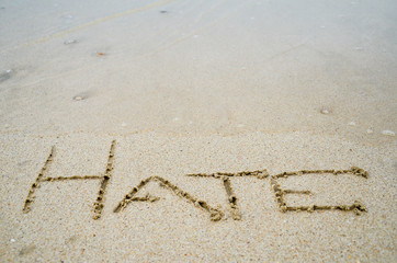 Abstract sign of word hate written on a sand beach background