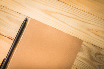 Brown note book with pen on wood background