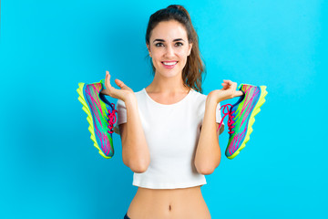 Happy young woman holding shoes