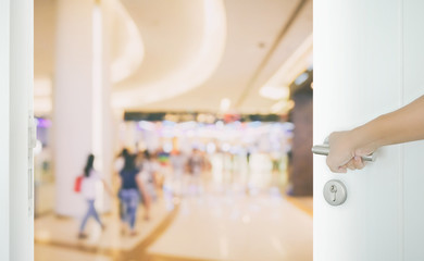 man hand opening white door to department store with people shopping as background.
