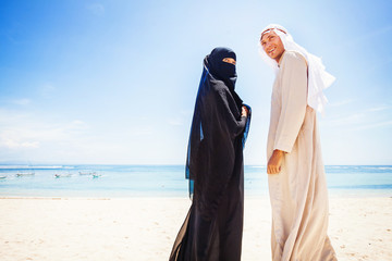 muslim couple on a beach wearing traditional dress