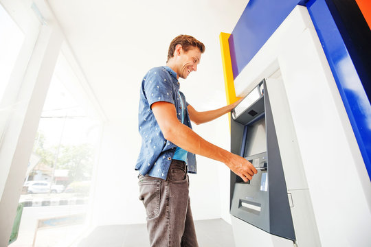 man using atm to withdraw cash