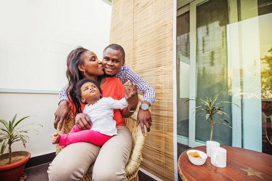 adorable african family at balcony having tea