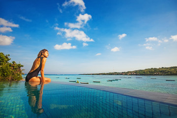 woman sitting on the edge of infinity pool with stunning view