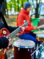 Male buskers on autumn outdoor play guitar. Cool weather.
