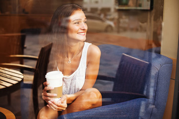 beautiful young lady having coffee or tea at cafe
