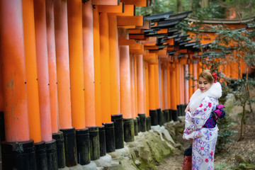 Woman dressed in traditional japanese costume walking under tori